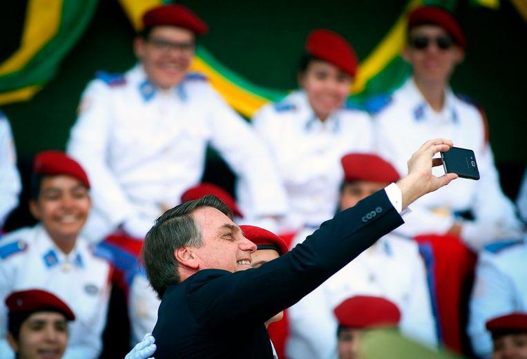 De Braziliaanse president Jair Bolsonaro maakt een selfie met een student van een militaire academie op het hoofdkwartier van het Braziliaanse leger in de hoofdstad Brasília tijdens een ceremonie ter gelegenheid van de Dag van de Soldaat die vrijdag in Brazilië werd gevierd. Beeld null