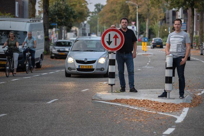 Buurtbewoners onder wie Joop van Odenhoven (l) protesten tegen de verkeersoverlast in hun straat.