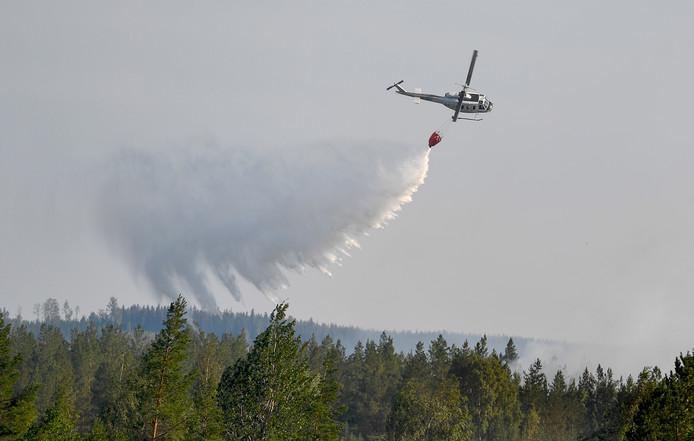 Een helikopter helpt uitbreiding van het vuur naar een gebied met woningen te voorkomen bij Ljusdal.