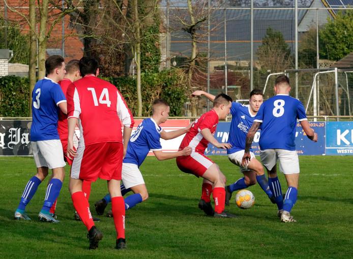 Kluitjesvoetbal in Noordhoek. Een aanvaller van de thuisploeg (rode shirts) wordt belaagd door drie spelers.