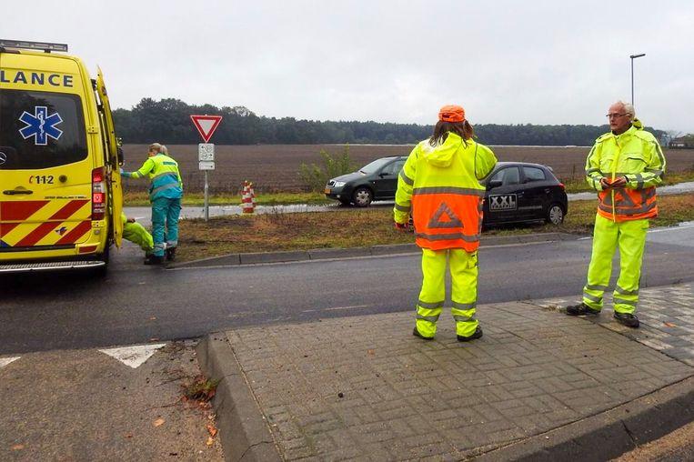 Jim van Kooten zit links in de ambulance, terwijl toegesnelde collega's toekijken