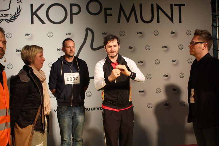 Lievens Scheire bepaalt met muntworp wie naar de finale mag. Kandidaten Sofie Van Lysebeth, Nicolas De Corte en Kim Van Cauwenberghe kijken vol spanning toe.