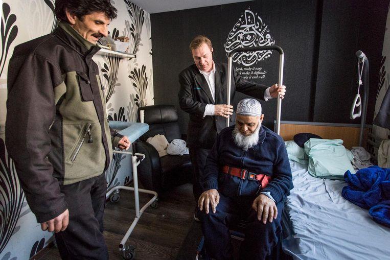 Mahboob Akthar wordt in een speciale stoel gezet en naar beneden getild door Transvisionchauffeur Guus Mozes (midden) en tilassistent Jamal Kalmoua Beeld Dingena Mol