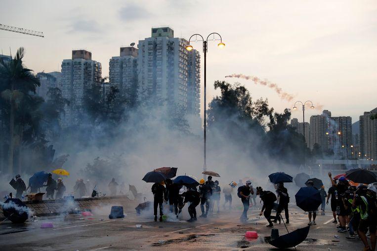 Demonstranten gooien traangas terug naar de politie.