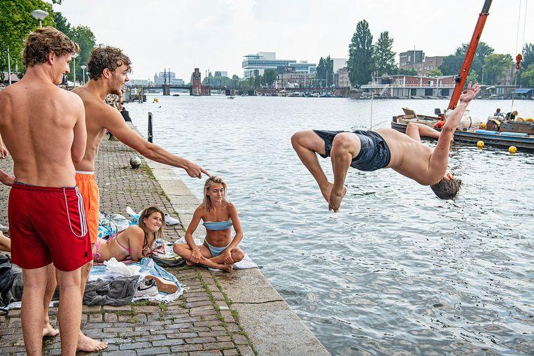 Jongeren genieten van het weer aan de Amstel in Amsterdam.  Beeld Guus Dubbelman / de Volkskrant