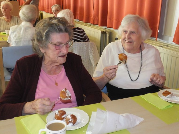 Antoinette en Yvonne smullen van hun oliebollen.