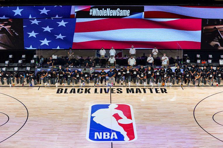 Spelers van de New Orleans Pelicans en Utah Jazz met een knie op de grond tijdens het volkslied.  Beeld Getty Images