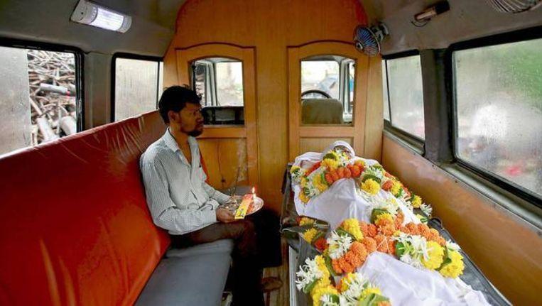 Een nabestaande zit in een lijkwagen in Mumbai bij het lichaam van een slachtoffer van illegale, giftige alcohol.
