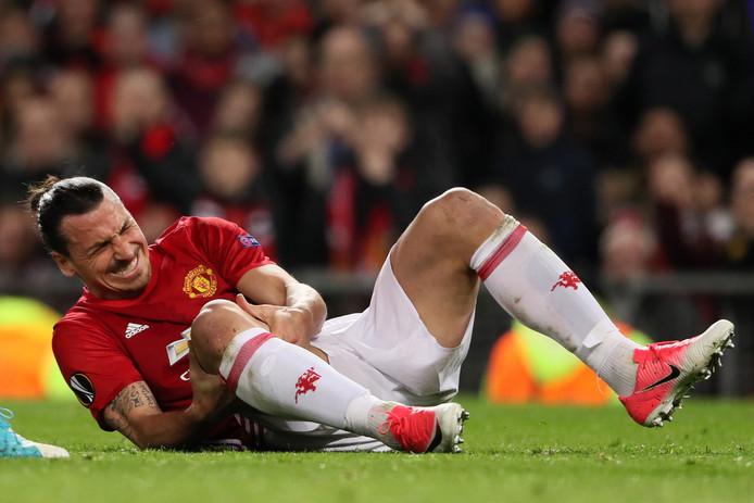 Zlatan Ibrahimovic kijkt met pijn en zorgen naar zijn knie na zijn vervelende val.