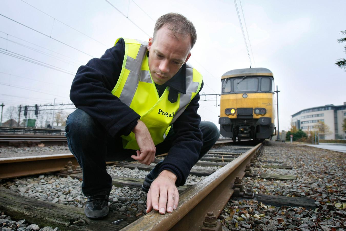 Een medewerker van ProRail controleert het spoor op schade door bladeren.