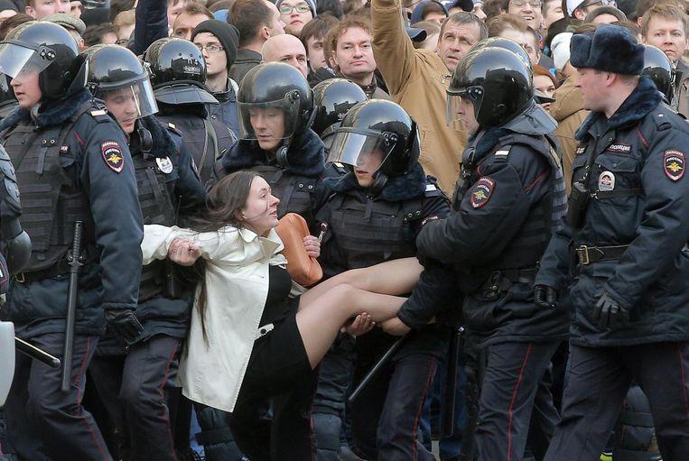 Politie draagt een vrouwelijke demonstrant weg. Beeld epa
