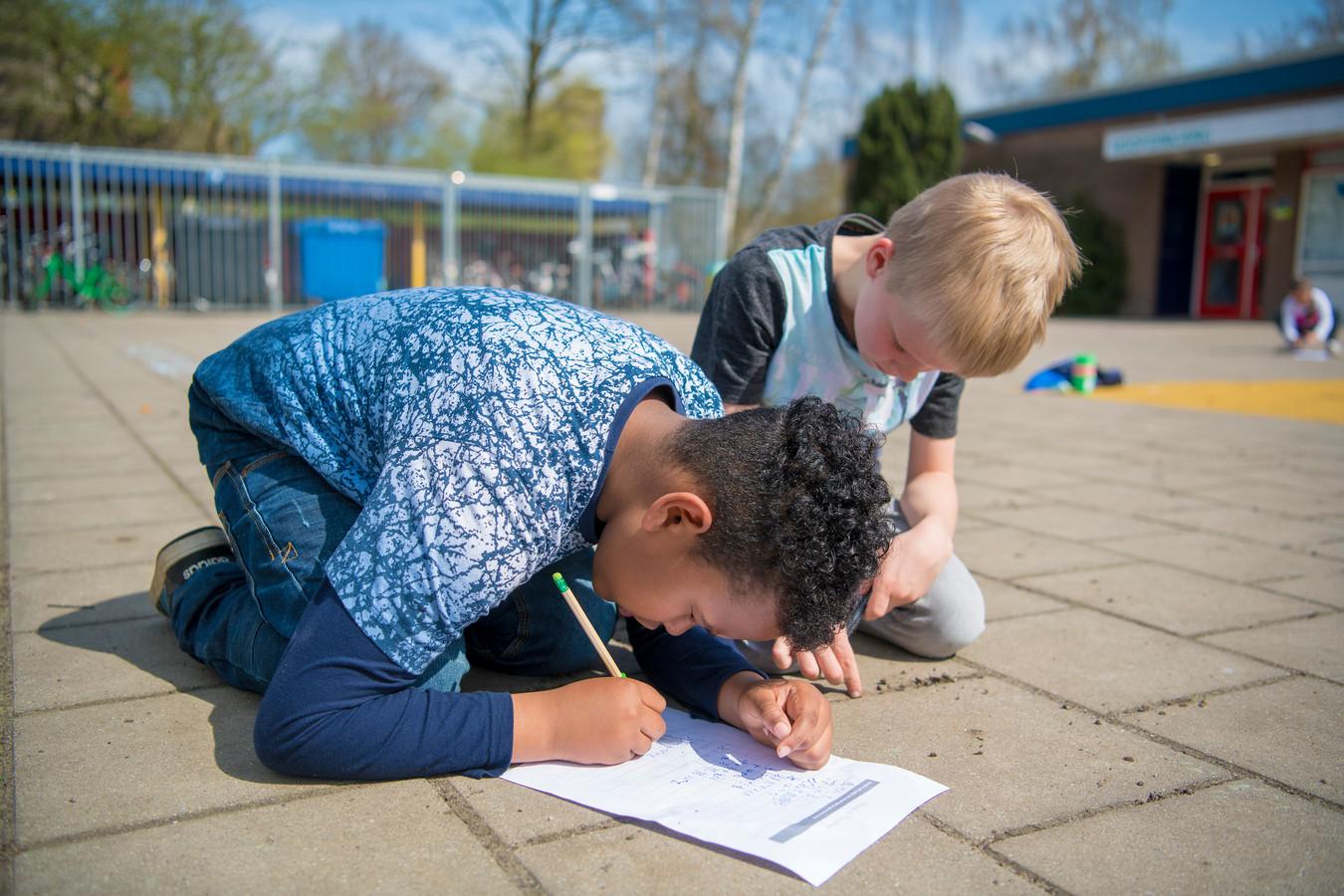 Leerlingen van groep 4 zijn druk bezig met de taalles op het schoolplein tijdens de Nationale Buitenlesdag op de PC Daltonschool Ichthus.