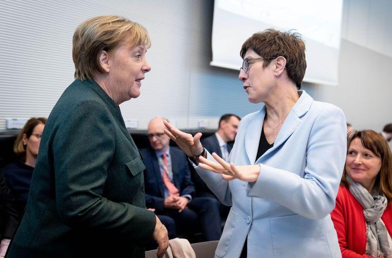 Annegret Kramp-Karrenbauer (r) in gesprek met Angela Merkel. Beeld Kay Nietfeld/dpa