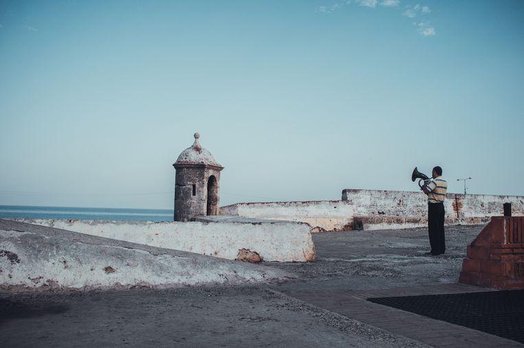 Een muzikant speelt vanaf de oude stadsmuur die je een prachtig uitzicht geven op de Caribische zee. Beeld Stijn Hoekstra