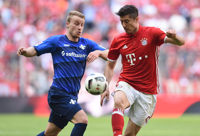 Fabian Holland van Darmstadt probeert Robert Lewandowski van de bal te zetten.