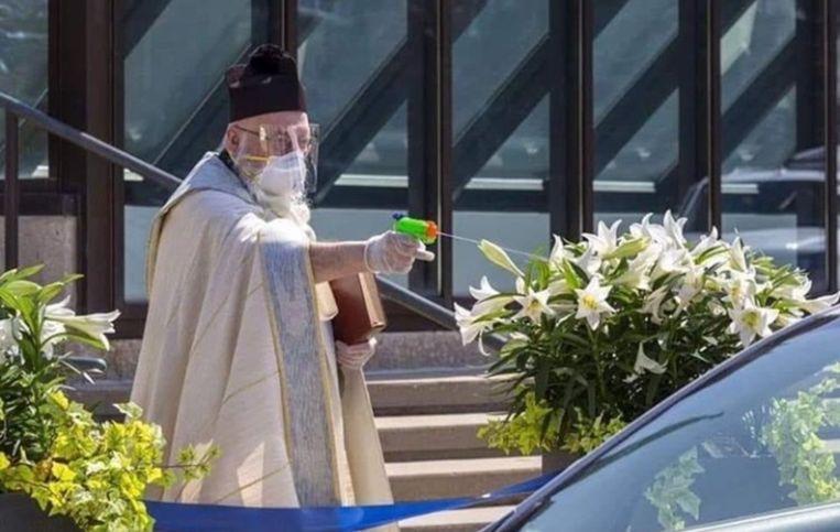 Priester schiet wijwater op kerkgangers tijdens de pandemie.