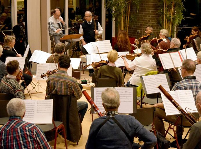 Repetitie van het RSO. Vooraan dirigent Jacco Nefs met daarnaast tarspeler Vahid Tarzen. Rechts vooraan zit initiatiefnemer Babash Azerei.