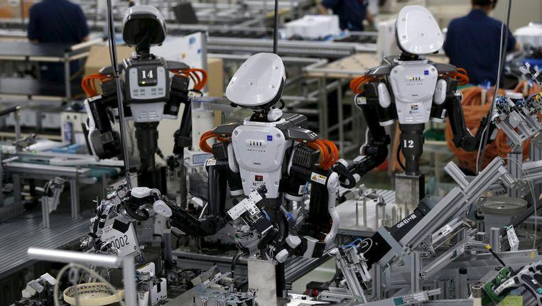In de assemblagelijn van de Japanse Glory-fabriek worden steeds meer robots naast gewone werknemers opgesteld. Beeld reuters