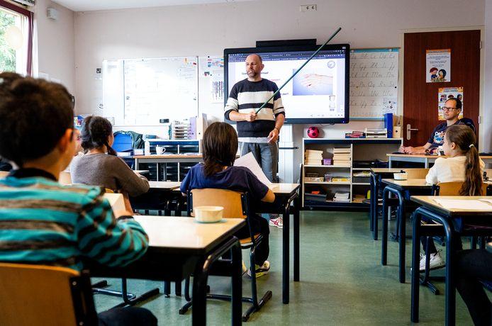 Een leraar laat met een stok aan basisschoolleerlingen zien wat 1,5 meter is.