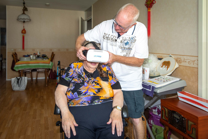 Vrijwilliger Wim Dongen zet de VR-bril op bij Cobie van der Velden.