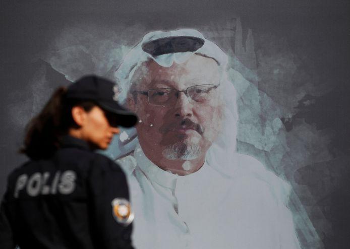 Een Turkse politieagente loopt langs een afbeelding van de vermoorde journalist Jamal Khashoggi.