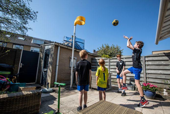 Tim gooit een bal richting de korf. Links van hem in het gele shirt staat Eline, tussen hen in staat Daan en helemaal links is Ruben.