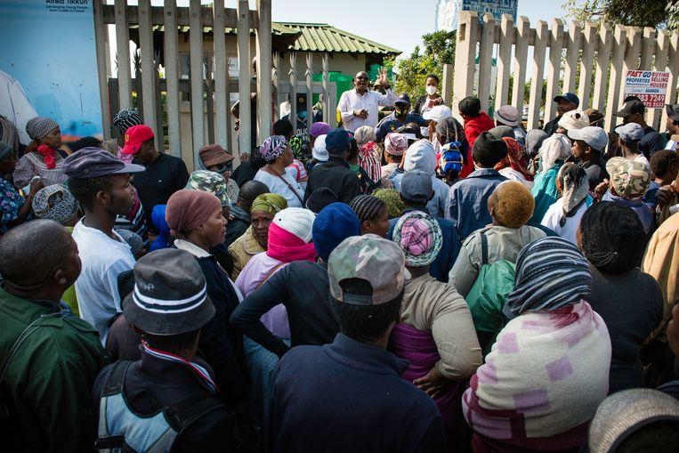 Manager Sipho Mamize bericht de menigte voor het buurtcentrum Wings of Life dat Afrika Tikkun vandaag op deze plek geen voedselpakketten uitdeelt. Beeld Bram Lammers
