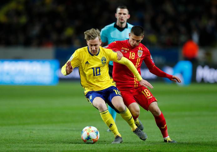 Razvan Marin namens Roemenië in duel met Emil Forsberg van Zweden.