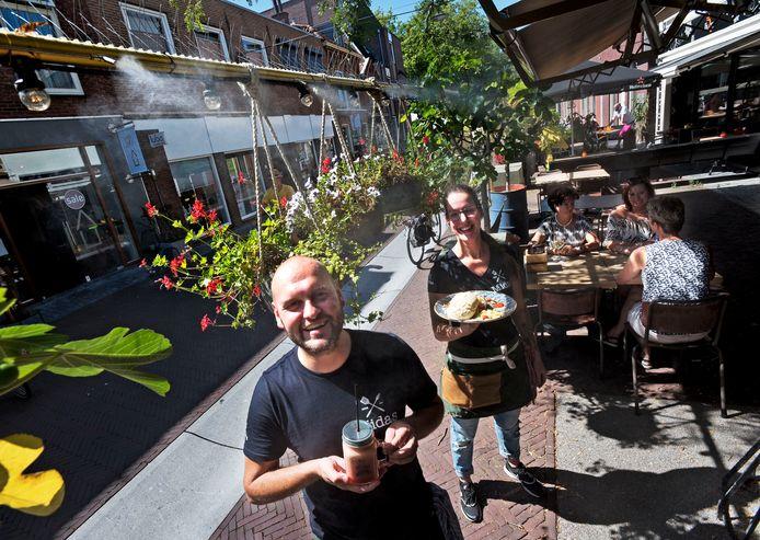Rick Vianen en Kimberly De Kruyf op het terras van Broodje Midas waar ter verkoeling een watervernevelaar is aangebracht.