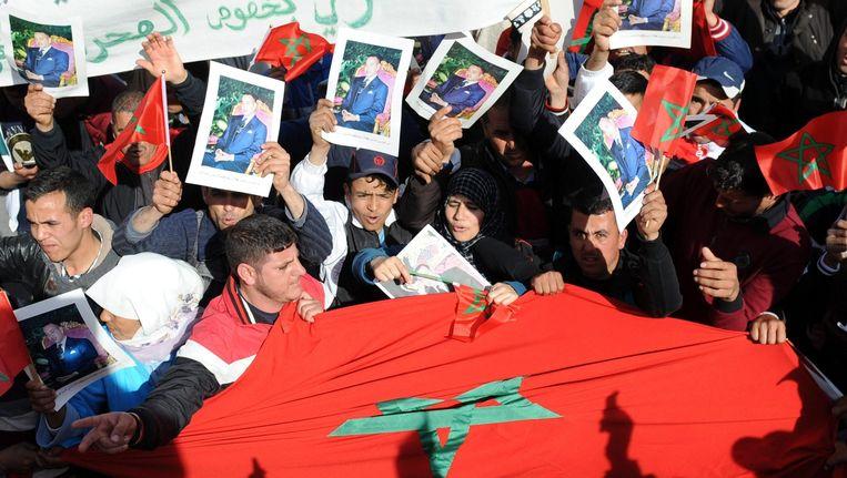 Marokkaanse demonstranten tonen de nationale vlag en een foto van de koning Mohammed VI. Beeld epa
