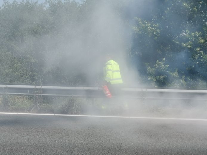 De chauffeur doet zijn best met een brandblusser uit zijn vrachtwagen maar kan het vuur niet doven langs de A12.