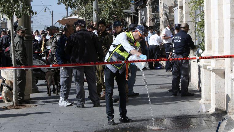 Een politieagent spoelt bloed van de straat weg. Beeld afp