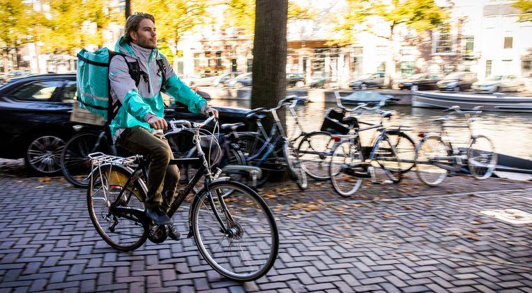 Een bezorger van Deliveroo in het centrum van Amsterdam. Beeld Hollandse Hoogte /  ANP