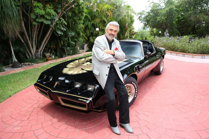 Acteur Burt Reynolds en zijn Pontiac Trans Am uit 1977