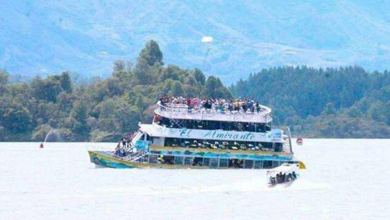 Passagiers van de zinkende boot staan uit voorzorg zoveel mogelijk op het bovenste dek.