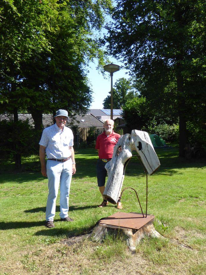 Beeldhouwer Sjef Cox (l) en campinghouder Hans Koop bij een beeld gehakt uit een vertakte stam van een appelboom. Verend opgesteld door middel van stalen strippen op dito voetplaat.
