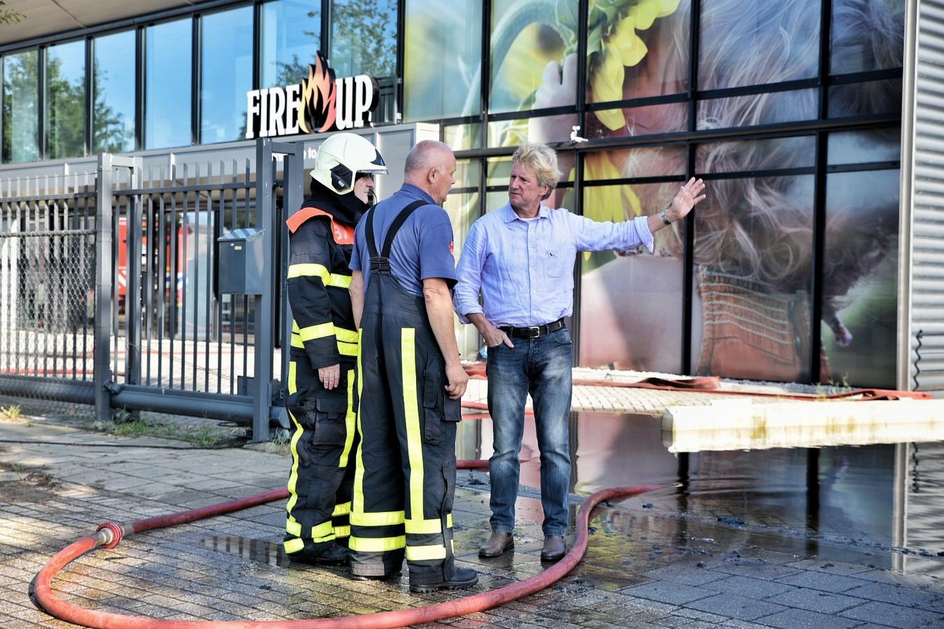 Kees van Opstal, eigenaar van Fire-Up, laat zich na de brand van eind juli bijpraten door de brandweer