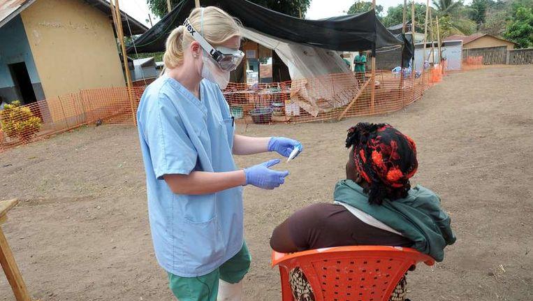 Een medewerker van artsen zonder grenzen helpt een mogelijk slachtoffer van het Ebola virus in Guinea. Beeld afp