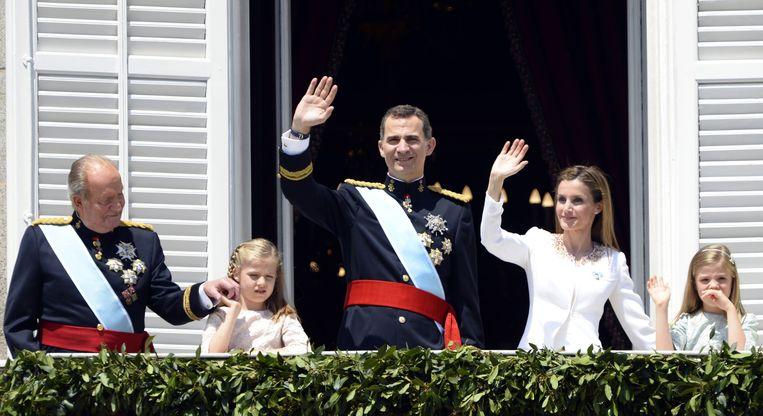 Juan Carlos (links), prinses Leonor, Felipe VI, Letizia en prinses Sofia zwaaien naar het publiek vanaf het balkon van het Koninklijke Paleis. Beeld afp