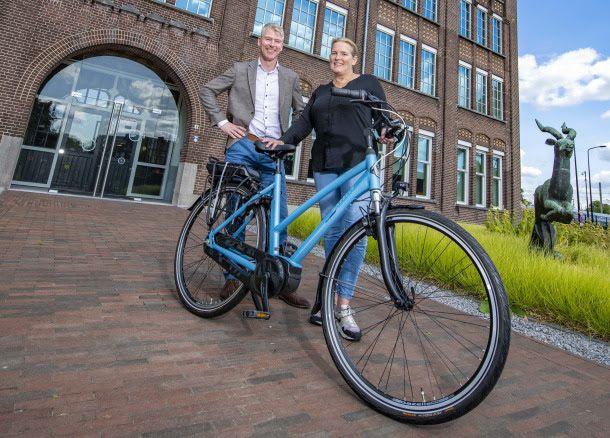 Elske Nijdam (r) krijgt van Gazelle-productieleider Gerco Oosterink een fiets omdat zij de Dierense fabriek snel attent maakte op de brand die daar begin juni uitbrak.
