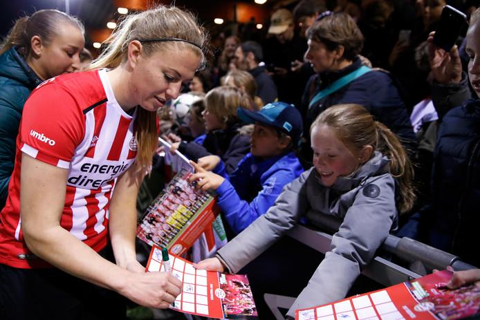 PSV-speelster Mauri van de Wetering deelt handtekeningen uit aan fans.