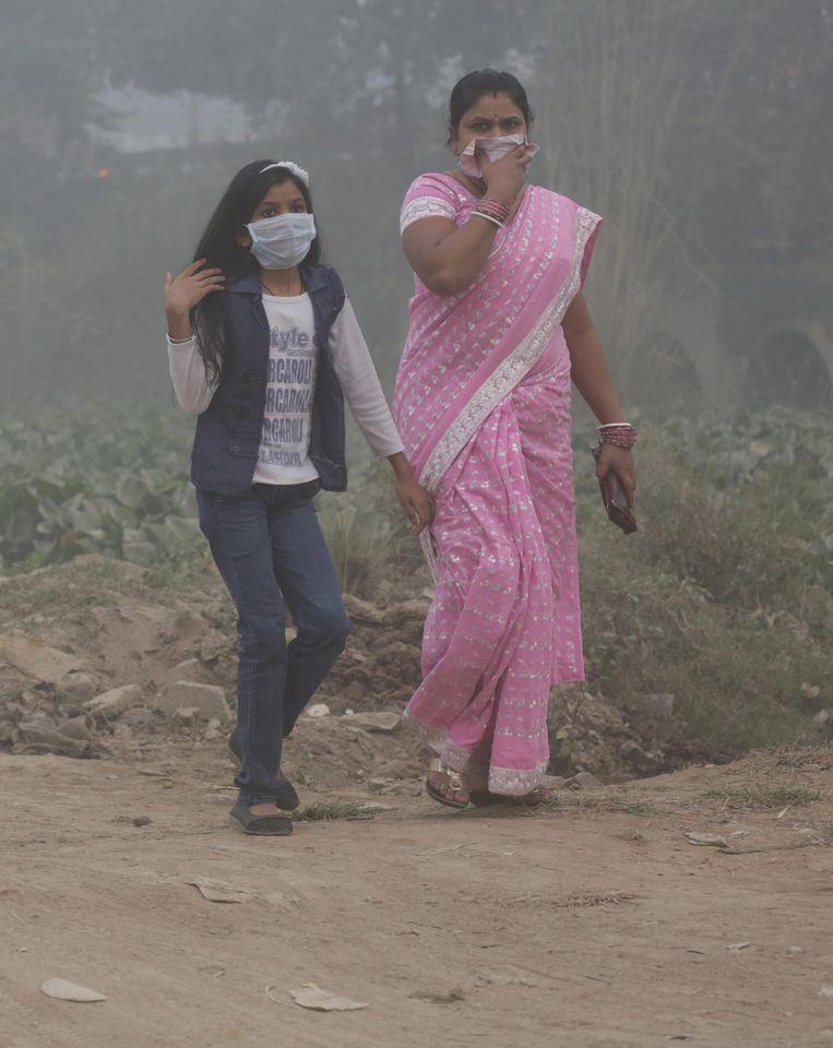 Twee Indiase vrouwen bedekken hun gezicht terwijl ze door zware stof en smog lopen in New Delhi, India. Beeld epa