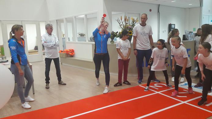 Ex-waterpolo-international Mieke Cabout (midden) geeft het startschot, drie meiden staan klaar om weg te rennen. Ex-schaatskampioen Annamarie Thomas (links) kijkt toe.