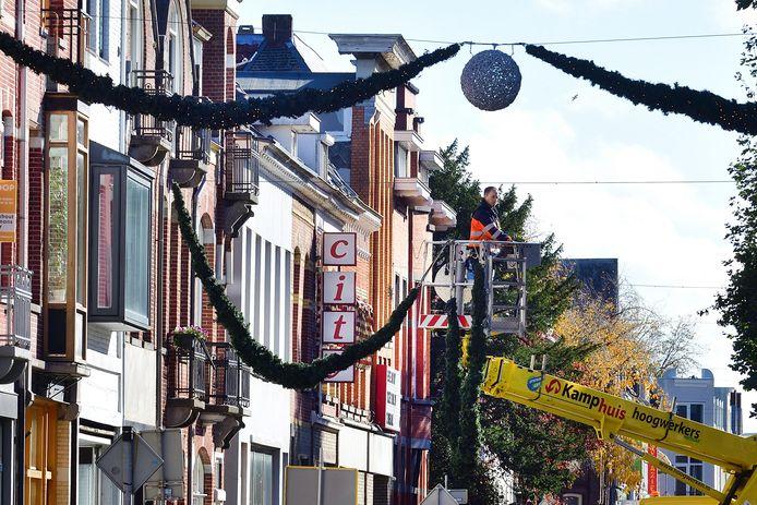 Met een hoogwerker wordt in de Brugstraat de feestverlichting opgehangen.