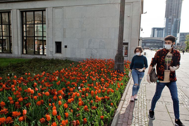 Jongeren met mondkapjes op bij een tulpenveld op het busstation van Warschau. Een aantal maatregelen om de verspreiding van het coronavirus tegen te gaan is versoepeld, waardoor er weer meer mensen de straat opgaan. Beeld Piotr Malecki