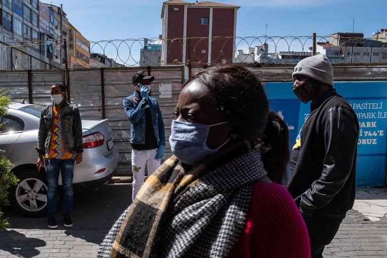 Leden van een liefdadigheidsnetwerk delen handschoenen, gezichtsmaskers, ontsmettingsmiddelen en voedselbonnen uit aan Afrikaanse migranten in Istanbul, op 17 april 2020.   Beeld AFP