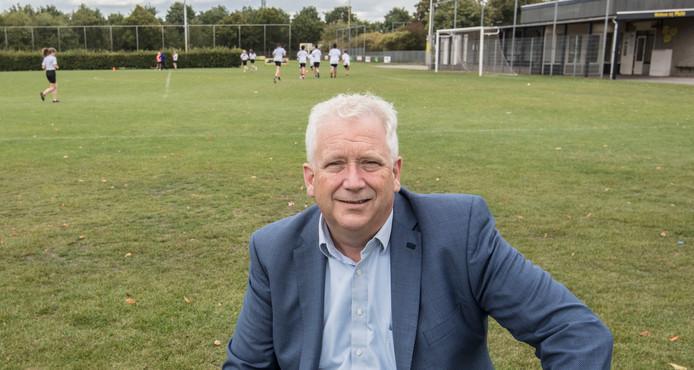 MULO-voorzitter Arjen Vos op sportpark De Braak in Helmond. Op de achtergrond de sportende leerlingen van het Dr. Knippenbergcollege.