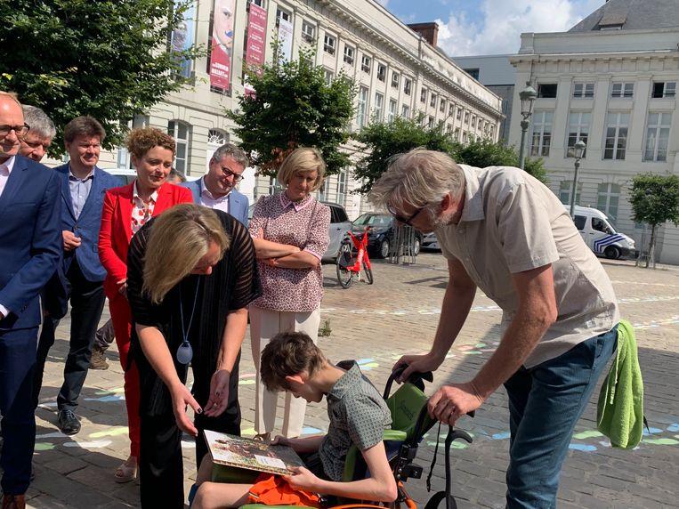 Janosch Dupont (14) overhandigt Vlaams minister-president Liesbeth Homans een kunstwerk in naam van de 20.000 patiënten die wachten op steun.