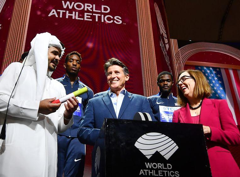 IAAF-voorzitter Sebastian Coe ziet op de slotceremonie hoe de Qatarese sjeikh Khalifa Al-Thani de symbolische stok doorgeeft aan Oregon en afgevaardigde Kate Brown (r).
