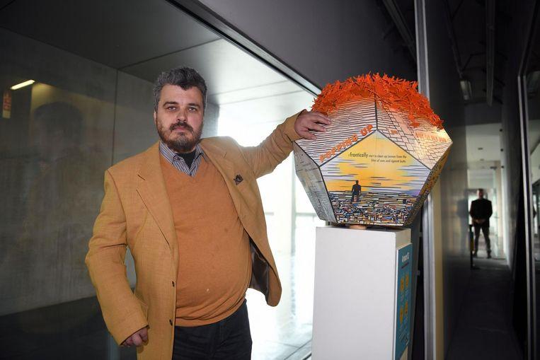 Jeroen, die lijdt aan psychoses, poseert bij het kunstwerk 'The invasion of the Oranges' in het Provinciehuis.